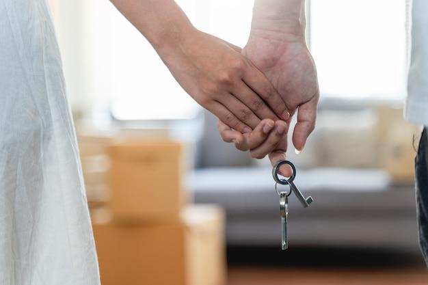 Mão de um jovem casal feliz entregando as chaves da nova casa em frente à porta de uma casa aberta