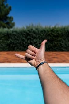 Mão de um jovem caucasiano mostrando os dedos sobre o fundo desfocado da piscina azul gesticulando gesto de saudação do shaka havaiano, telefone e símbolo de comunicação