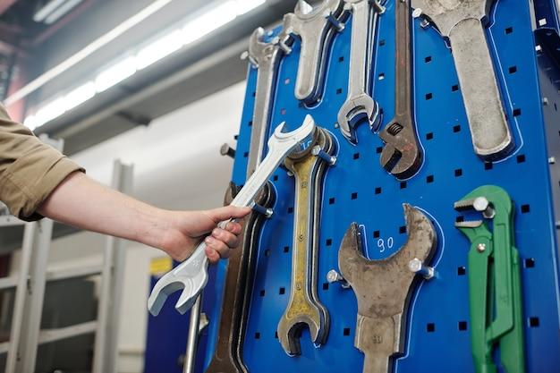 Mão de um jovem engenheiro ou outro trabalhador da planta industrial segurando uma grande chave inglesa perto do painel com ferramentas manuais semelhantes