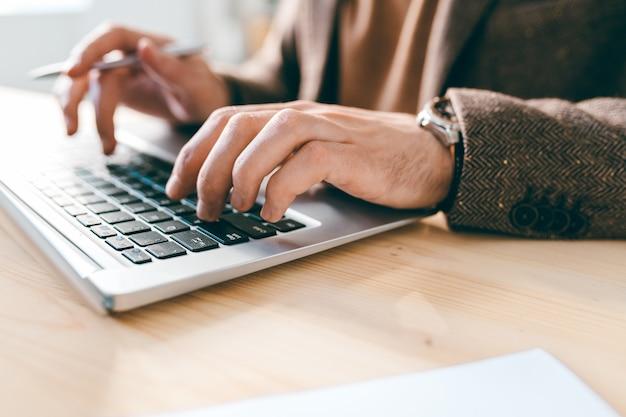 Mão de um jovem funcionário ou analista sobre o teclado do laptop durante o trabalho com novos dados na mesa de madeira no escritório