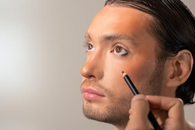 Mão de um jovem maquiador com delineador preto kohl vai aplicá-lo nos olhos de um modelo masculino
