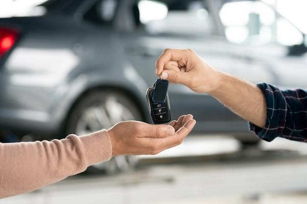 Mão de um jovem reparador dando o controle remoto do sistema de alarme a um cliente do sexo masculino após reparar o automóvel no interior da oficina