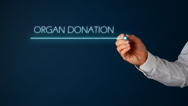 Mão de um médico escrevendo um sinal de doação de órgãos com uma caneta sobre fundo azul. com espaço de cópia.