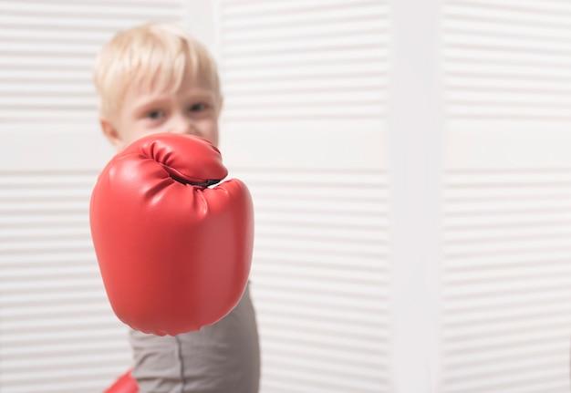Mão de um menino em uma luva de boxe vermelha. fechar-se