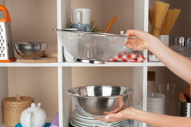 Mão, de, um, mulher, levando, kitchenware, de, um, cozinha, prateleira