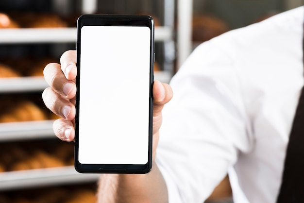 Mão de um padeiro masculino, mostrando a tela branca do telefone móvel
