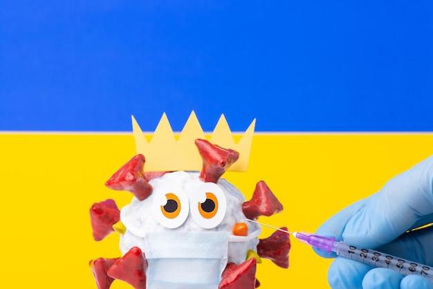 Mão de um trabalhador da área médica segurando uma seringa com vacina contra covid-19, bandeira ucraniana ao fundo