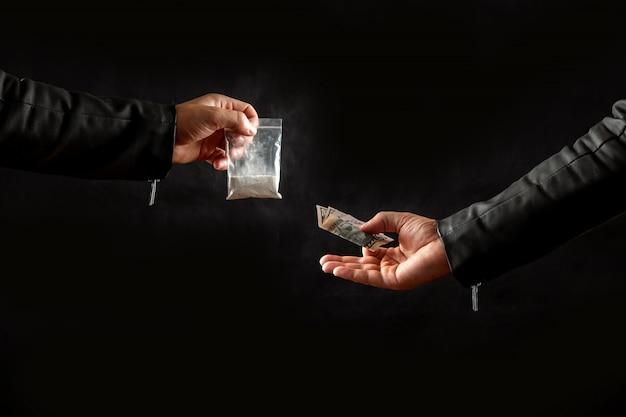 Mão de um viciado em drogas com dinheiro comprando uma dose de cocaína