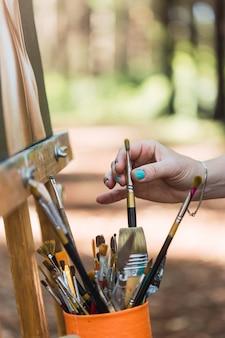 Mão de uma artista mulher segurando um pincel para pintar seu trabalho ao ar livre.