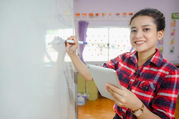 Mão de uma bela professora asiática segurando um tablet escrevendo no quadro branco, ensinando alunos na escola em sala de aula para educação