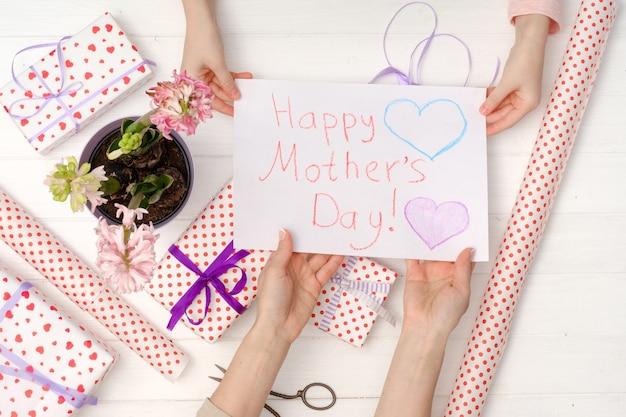 Mão de uma criança dando um cartão postal pintado à mão para a mão de sua mãe, vista superior. presentes para feliz dia das mães