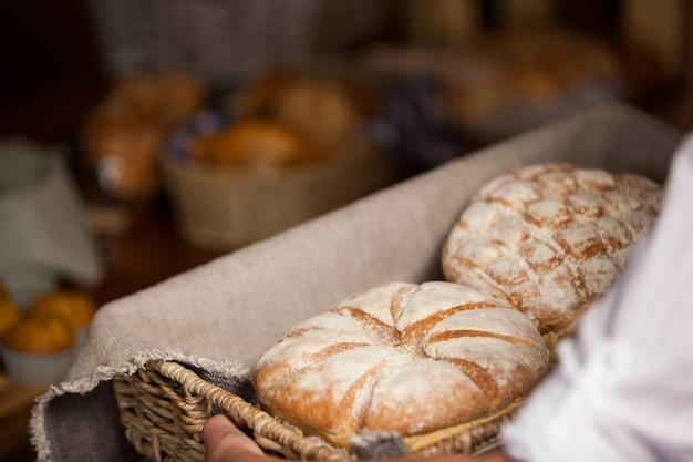 Mão de uma funcionária segurando uma cesta de alimentos doces na seção de padaria