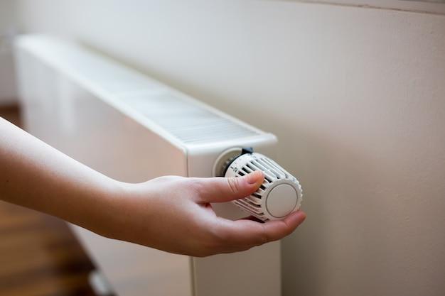 Mão de uma jovem alterando a temperatura no radiador pelo controlador de temperatura