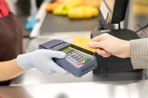 Mão de uma jovem caixa em uniforme e luvas de proteção segurando um terminal de pagamento, enquanto uma das consumidoras pagando com cartão de crédito