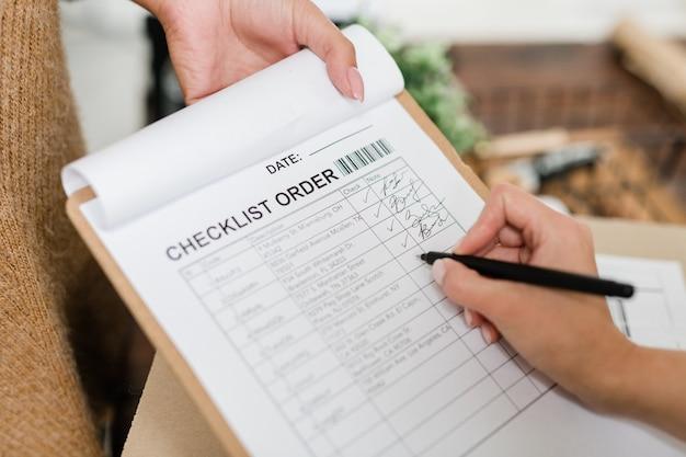 Mão de uma jovem com caneta vai marcar uma das posições na lista de verificação após receber o pedido