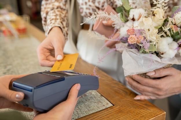 Mão de uma jovem compradora com buquê floral segurando um cartão de crédito sobre o terminal de pagamento no balcão enquanto paga por flores na floricultura