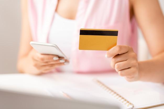 Mão de uma jovem compradora com um cartão de plástico usando smartphone em busca de uma promoção para fazer pedidos online