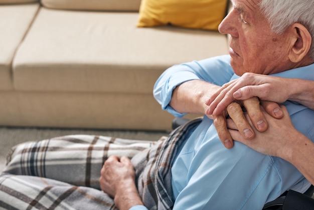 Mão de uma jovem cuidadora no ombro de um homem idoso com deficiência confortando-o e expressando empatia