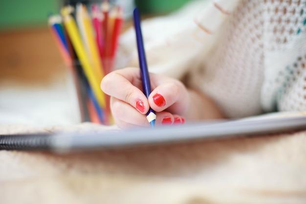 Mão de uma jovem desenhando uma imagem artística com giz de cera colorido