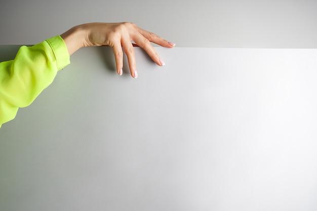 Mão de uma jovem em uma blusa brilhante sobre um fundo cinza com lugar para texto, close-up. linda manicure francesa. conceito de spa e manicure.