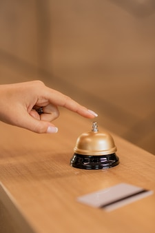 Mão de uma jovem empresária contemporânea pressionando o botão de chamada no anel no balcão da recepção do hotel
