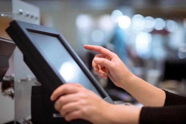 Mão de uma jovem fazendo o pagamento do processo em uma caixa registradora touchscreen, conceito de finanças