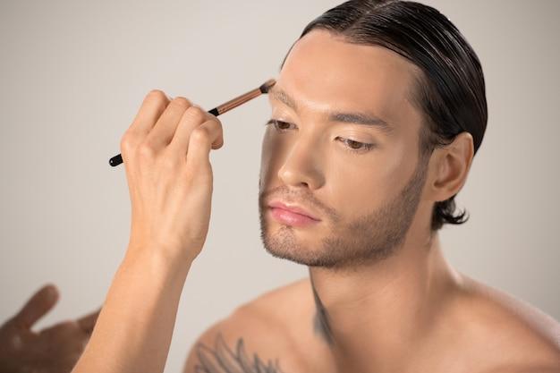 Mão de uma jovem maquiadora com pincel aplicando base na testa de modelo masculino com tatuagem no pescoço e ombro