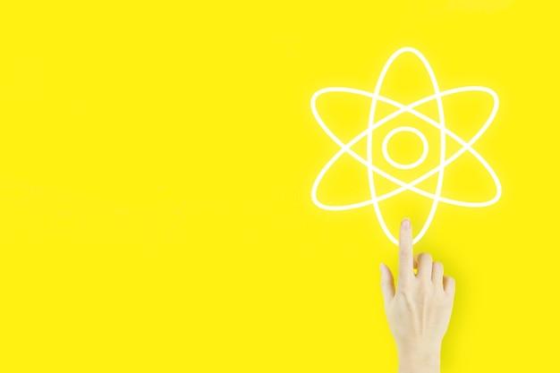 Mão de uma jovem mulher apontando o dedo com o símbolo do átomo da molécula de holograma em fundo amarelo.