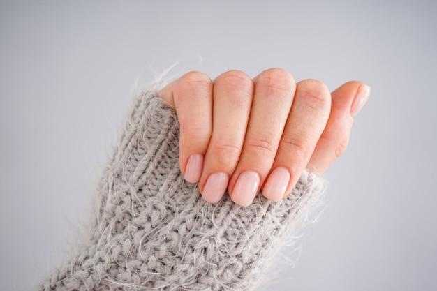 Mão de uma jovem mulher com uma bela manicure em um fundo cinza. manicure feminina. postura plana, close-up.