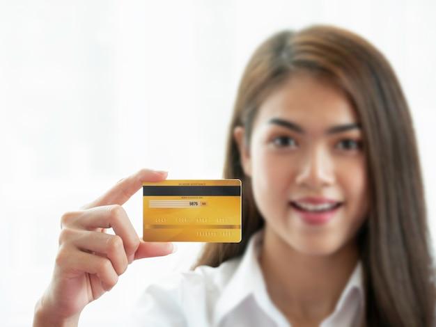 Mão de uma linda mulher asiática segurando o cartão de crédito