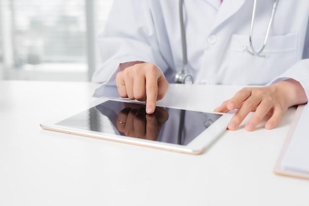 Mão de uma médica tocando um tablet digital enquanto está sentado na mesa.
