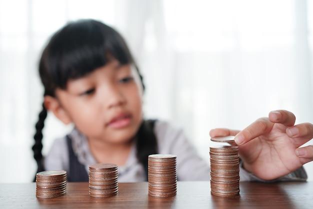 Mão de uma menina criança colocando moedas na pilha de moedas