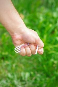 Mão de uma menina segurando o lixo plástico na grama verde do parque