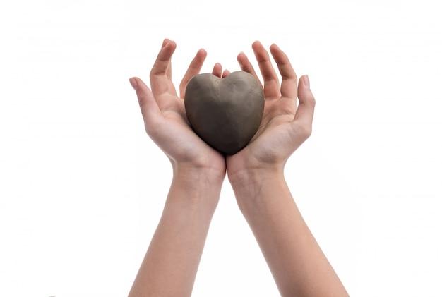 Mão de uma menina segurando um coração feito de barro. símbolo de amor e dia dos namorados.