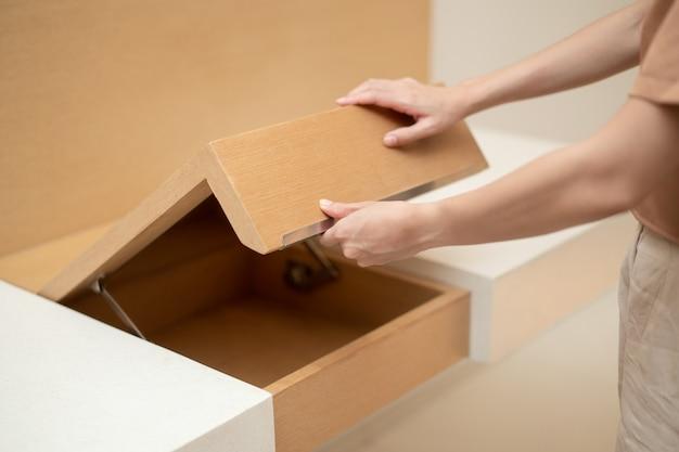Mão de uma mulher abrindo o armário da mesa de madeira marrom embutida.