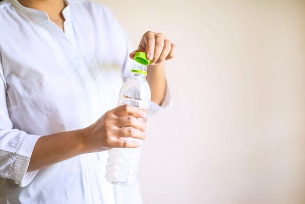 Mão de uma mulher abrindo uma garrafa com água