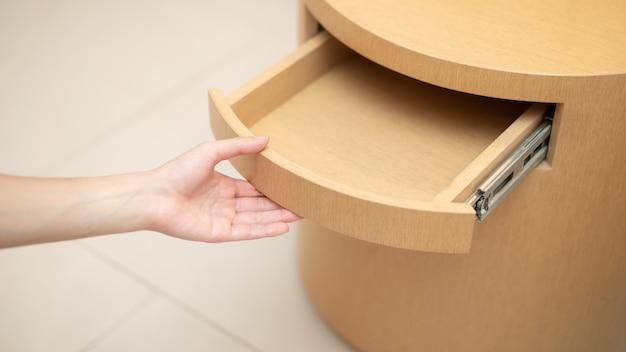 Mão de uma mulher abrindo uma gaveta na mesa de madeira.
