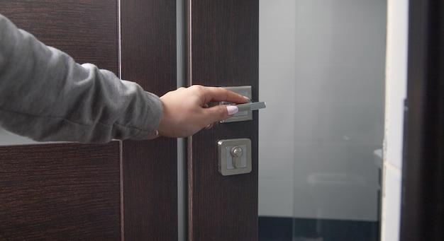 Mão de uma mulher abrindo uma porta em casa.
