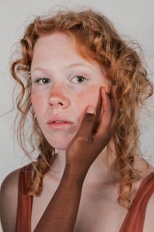 Mão de uma mulher africana tocando as bochechas de sua amiga loira