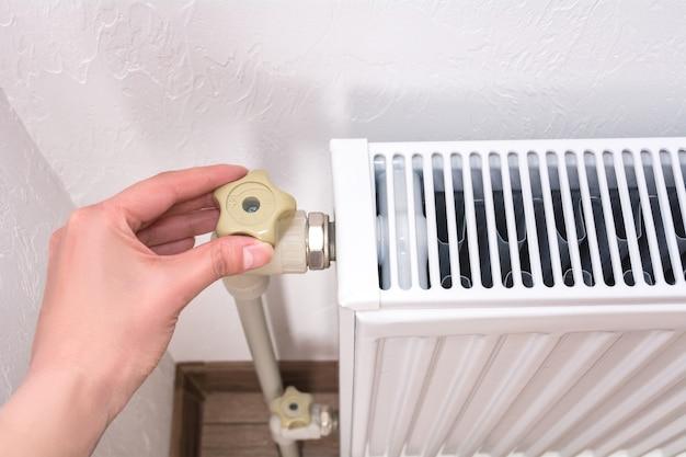 Mão de uma mulher ajustando o botão do radiador de aquecimento. conceito de custos de aquecimento caros