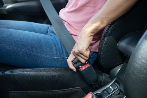 Mão de uma mulher apertando o cinto de segurança no carro, imagem recortada de uma mulher sentada no carro e colocando o cinto de segurança, conceito de condução segura.