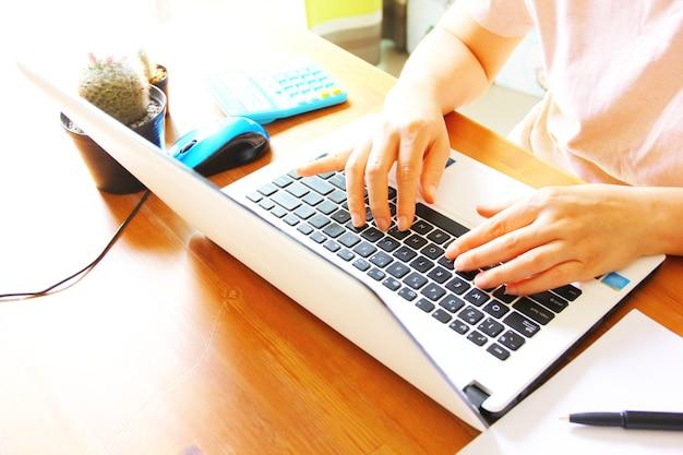 Mão de uma mulher asiática trabalhando com um aluno laptop usando um laptop em busca de informações on-line Foto Premium
