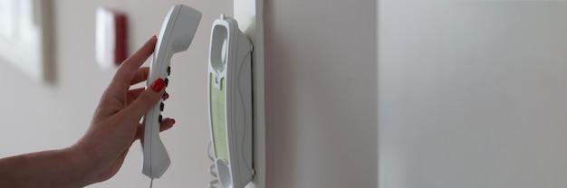 Mão de uma mulher atende o intercomunicador do apartamento
