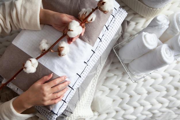 Mão de uma mulher bem cuidada segurando um galho de algodão com uma pilha de lençóis cuidadosamente dobrados perto de toalhas enroladas em uma cesta de malha colocada em uma manta de lã de merino grossa de malha. têxtil natural. vista do topo.