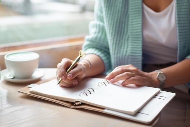 Mão de uma mulher bem preparada segurando uma caneta de ouro e escrevendo notas com caneta de ouro no caderno enquanto bebe café com leite azul ao lado da janela. jornalista freelance trabalhando em casa. planejando o conceito de futuro. copie o espaço