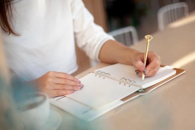 Mão de uma mulher bem preparada segurando uma caneta de ouro e escrevendo notas com uma caneta de ouro no caderno ao lado da janela