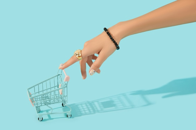 Mão de uma mulher bonita e elegante com um elegante anel segurando o carrinho de compras sobre fundo azul