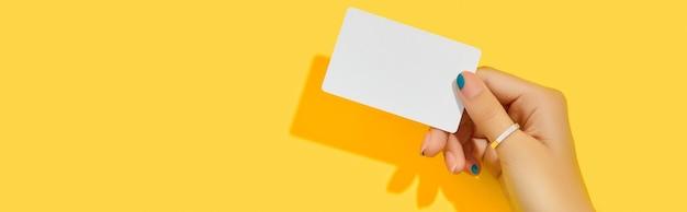 Mão de uma mulher bonita e elegante segurando um cartão de visita em fundo amarelo