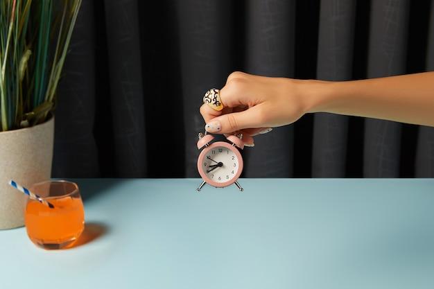 Mão de uma mulher bonita segurando o despertador na mesa azul