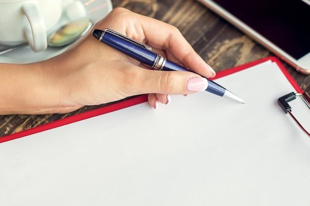Mão de uma mulher canhota fazendo anotações no bloco de notas no café.